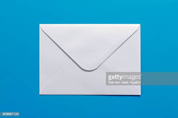 close-up of white envelope against blue background - envelope stock pictures, royalty-free photos & images