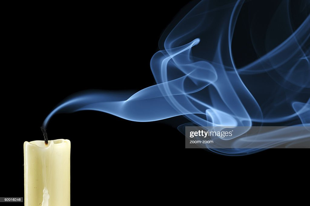 Close-up of white extinguished candle with curling up smoke : Stock Photo