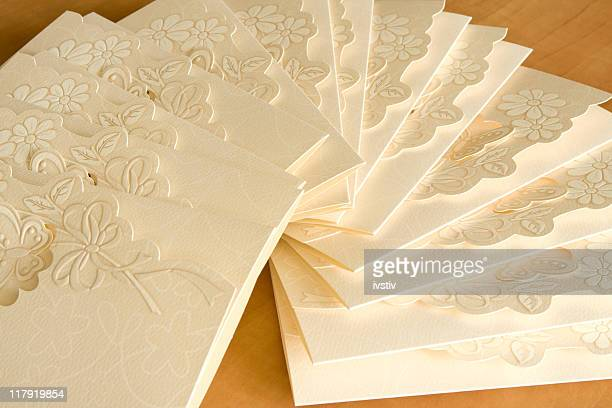 Close-up of white invitation cards with engraved flowers