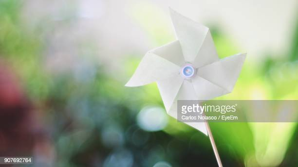 close-up of white pinwheel toy outdoors - paper windmill stock photos and pictures