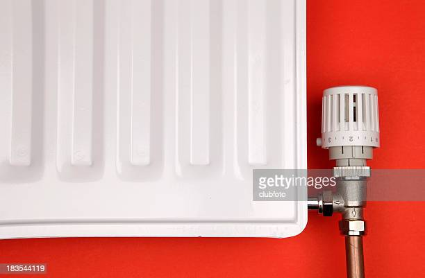 Closeup of white radiator and thermostatic valve