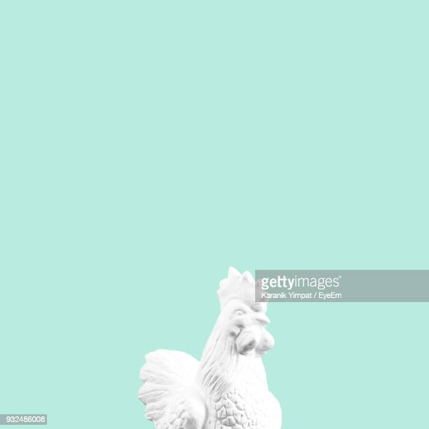 Close-Up Of White Rooster Statue Against Colored Background