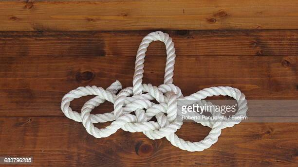 Close-Up Of White Rope On Wooden Surface