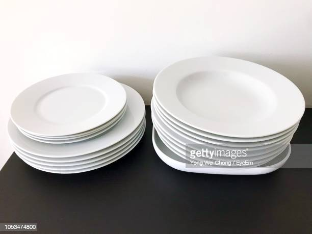 close-up of white saucers and plates on table - saucer stock pictures, royalty-free photos & images