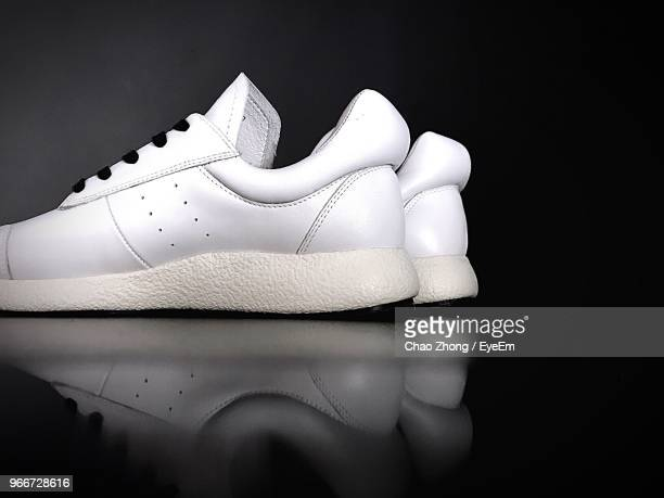 Close-Up Of White Shoes On Table In Darkroom