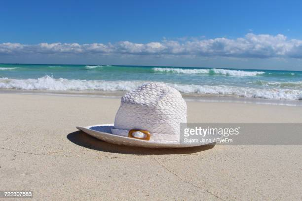 Close-Up Of White Sun Hat On Shore At Beach Against Sky