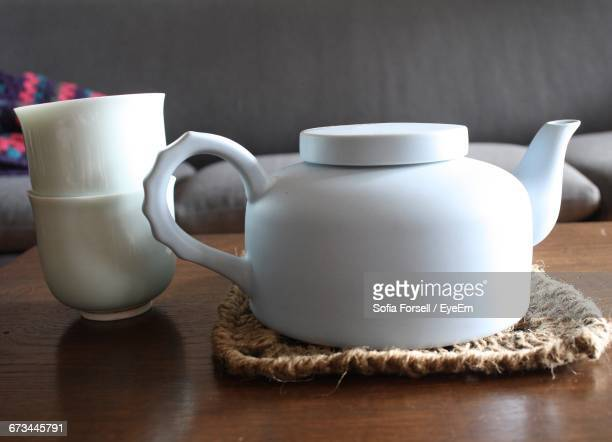 Close-Up Of White Teapot By Cup On Table At Home