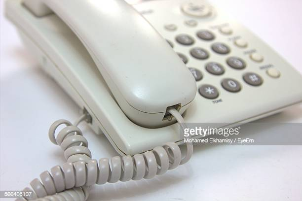 Close-Up Of White Telephone On Table