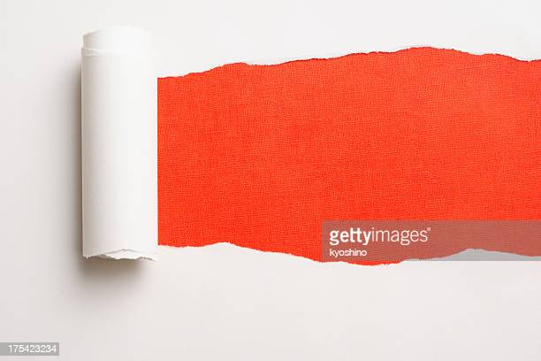 Close-up of white torn paper on orange background.