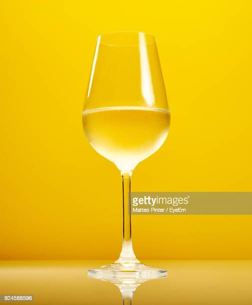 Close-Up Of White Wine Against Yellow Background