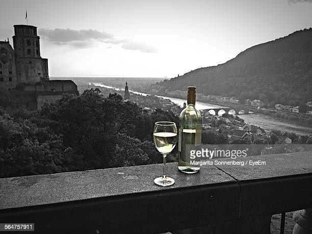 Close-Up Of White Wine In Glass And Bottle On Ledge With Fort In Background