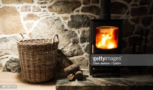 close-up of wicker basket by fireplace - wood burning stove stock photos and pictures