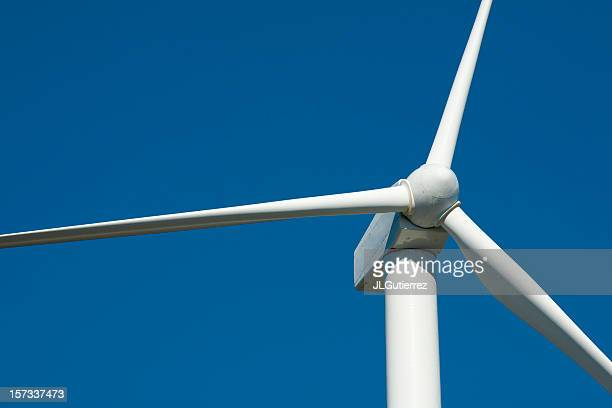 Close-up of wind turbine against blue sky