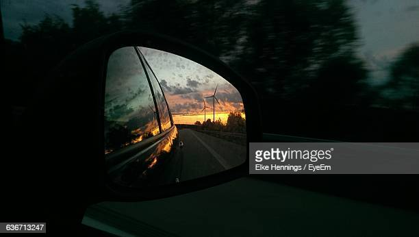 close-up of wind turbines against sky during sunset reflection in side-view mirror - vehicle mirror stock-fotos und bilder