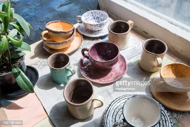 close-up of window-sill with potted plant and various multicolored ceramic cups with dishes - ceramic stock pictures, royalty-free photos & images