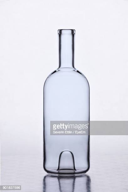 close-up of wine bottle on table against white background - liquor bottles stock pictures, royalty-free photos & images