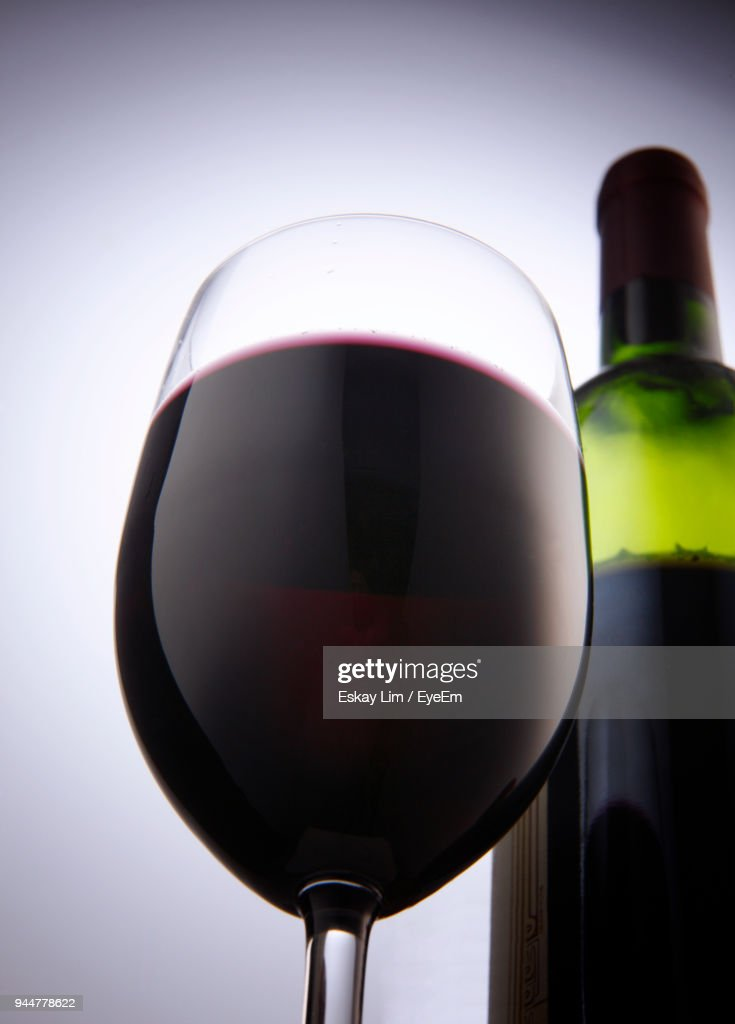 Close-Up Of Wine Bottle With Glass Against White Background : Stock Photo