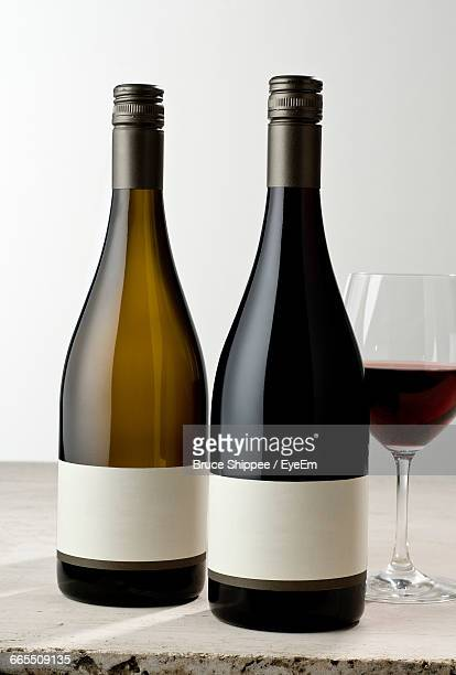 Close-Up Of Wine Bottles And Glass On Table