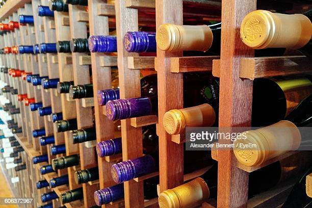 Close-Up Of Wine Bottles On Wooden Rack At Warehouse