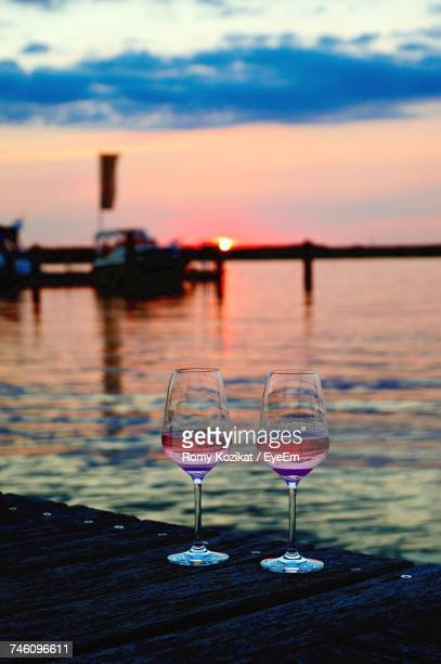 Close-Up Of Wine Glass By Sea Against Sunset