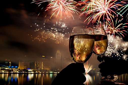 Close-Up Of Wine Glasses Toasting Against Fireworks At Night - gettyimageskorea