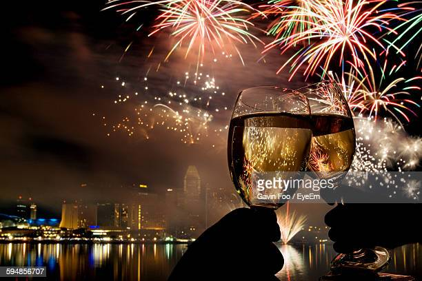 Close-Up Of Wine Glasses Toasting Against Fireworks At Night