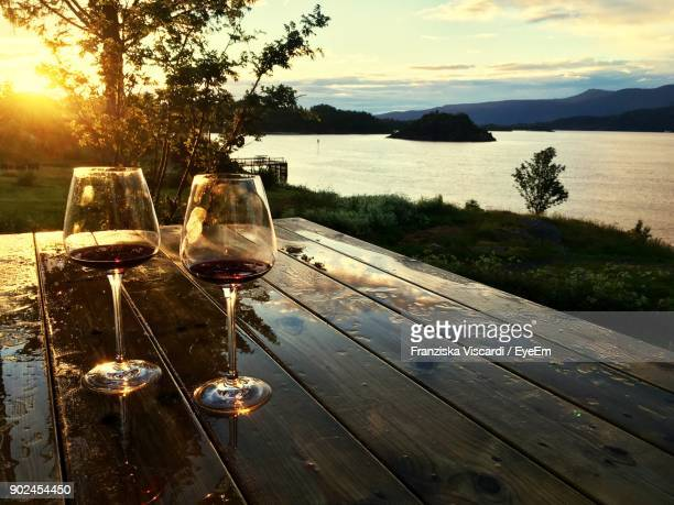 close-up of wine on table by lake during sunset - wine glass stock photos and pictures