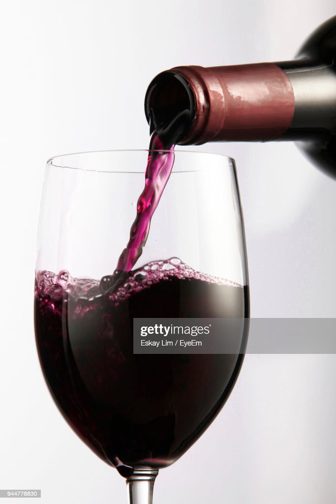 Close-Up Of Wine Pouring From Bottle In Wineglass Against White Background : Stock Photo