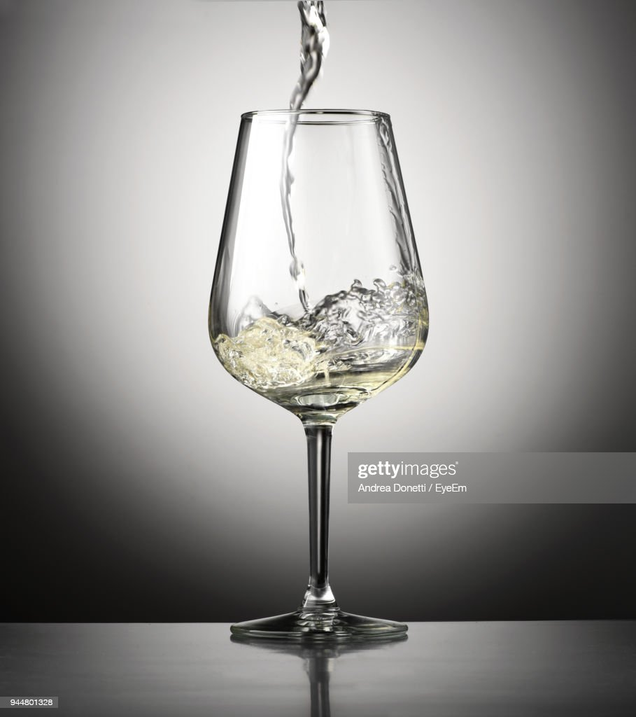 Close-Up Of Wine Pouring In Glass On Table Against Black Background : Stock Photo