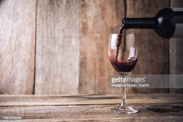 close-up of wine pouting in wineglass on wooden table - fülle stock-fotos und bilder