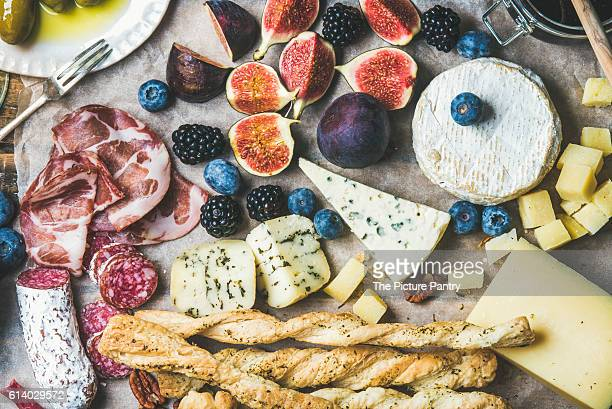 Close-up of wine snack set with meat variety, bread, green olives, figs, nuts and berries on wax paper