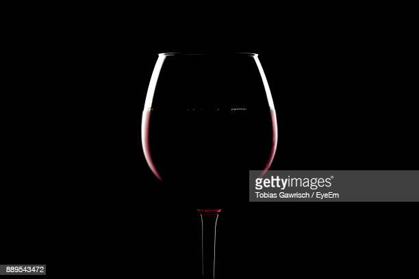 close-up of wineglass against black background - wine glass stock photos and pictures