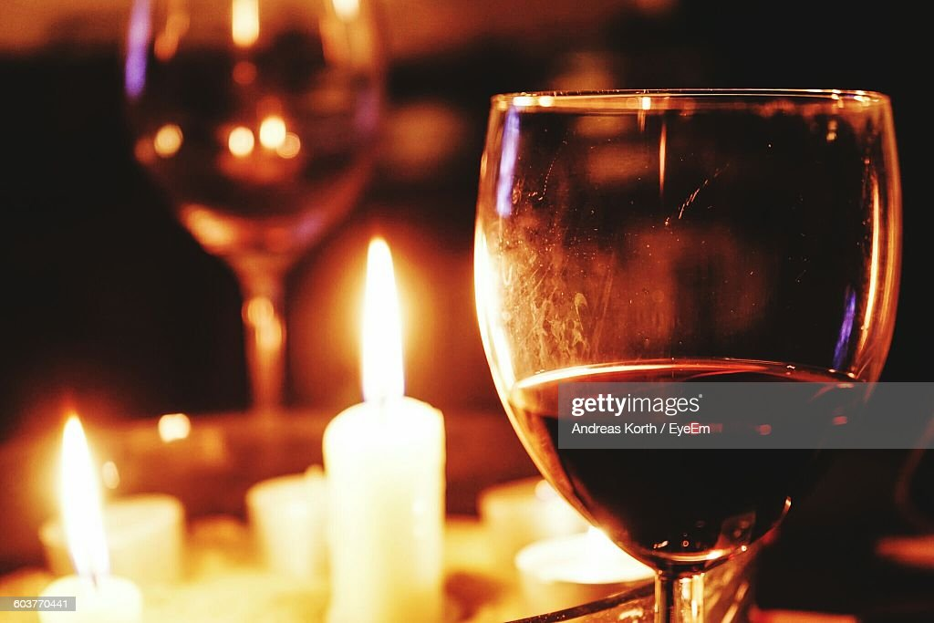 Close-Up Of Wineglass Against Lit Candle On Table : Stock Photo