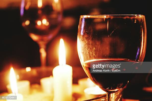 Close-Up Of Wineglass Against Lit Candle On Table