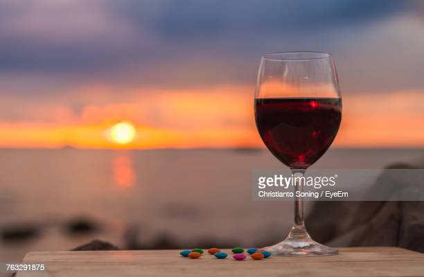 Close-Up Of Wineglass Against Sky During Sunset