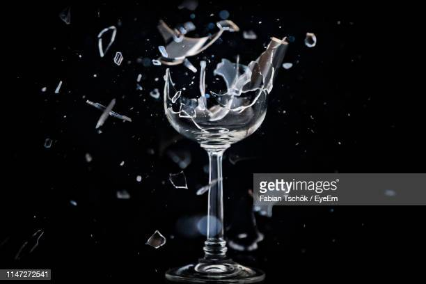 close-up of wineglass breaking against black background - 壊れた ストックフォトと画像
