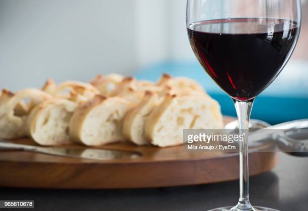 Close-Up Of Wineglass By Breads On Table