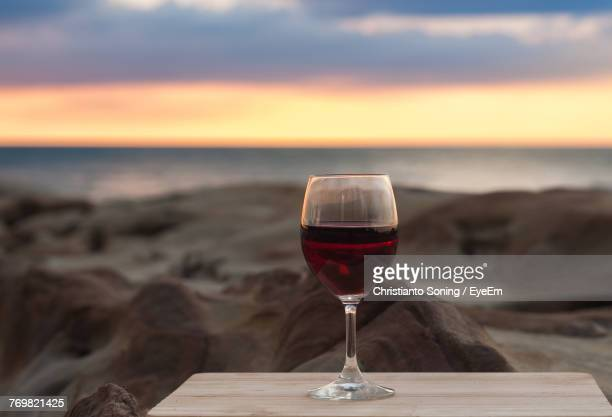 Close-Up Of Wineglass On Table Against Sea During Sunset