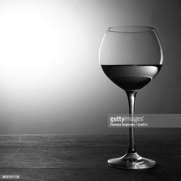 Close-Up Of Wineglass On Table Against Wall