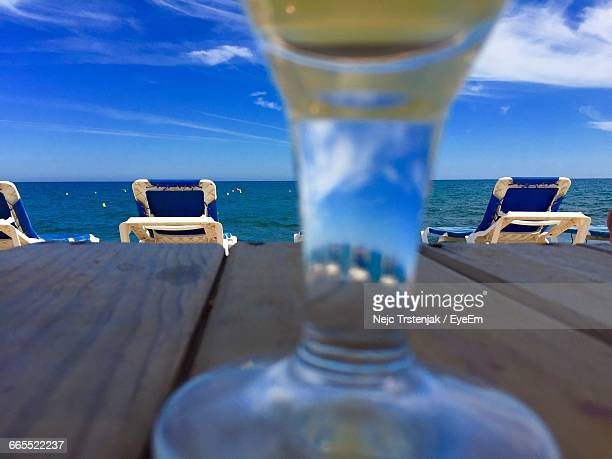 Close-Up Of Wineglass On Table By Sea Against Sky