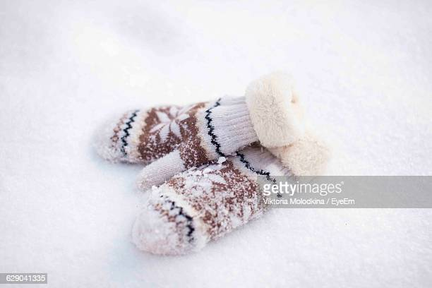 Close-Up Of Winter Gloves On Snow Covered Field