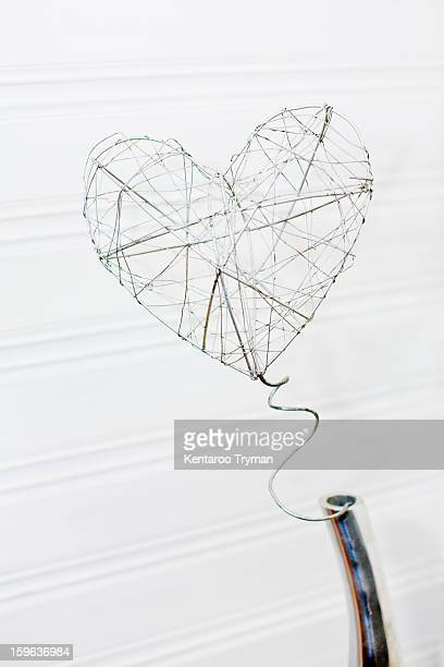 Close-up of wire forming heart shape over white background