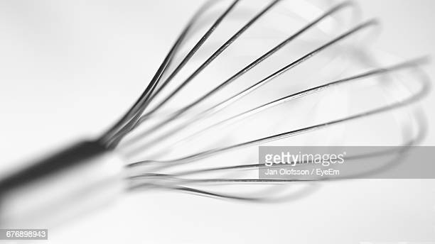 Close-Up Of Wire Whisk Against White Background