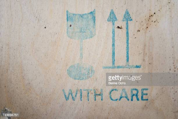 Close-up of WITH CARE sign on wooden crate