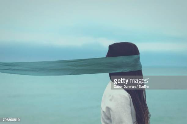close-up of woman against sea - blindfolded stock photos and pictures