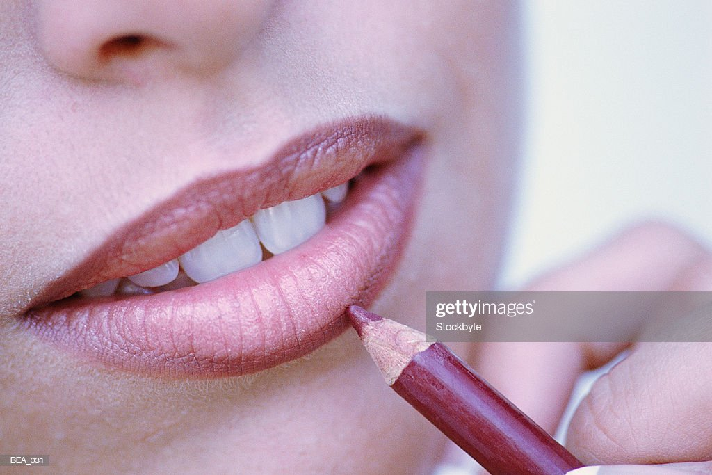 Close-up of woman applying lip liner : Stock Photo