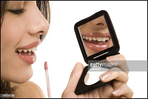 Closeup of woman applying lipstick with compact mirror