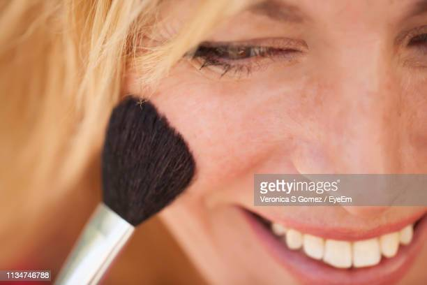 close-up of woman applying make-up - blusher stock pictures, royalty-free photos & images
