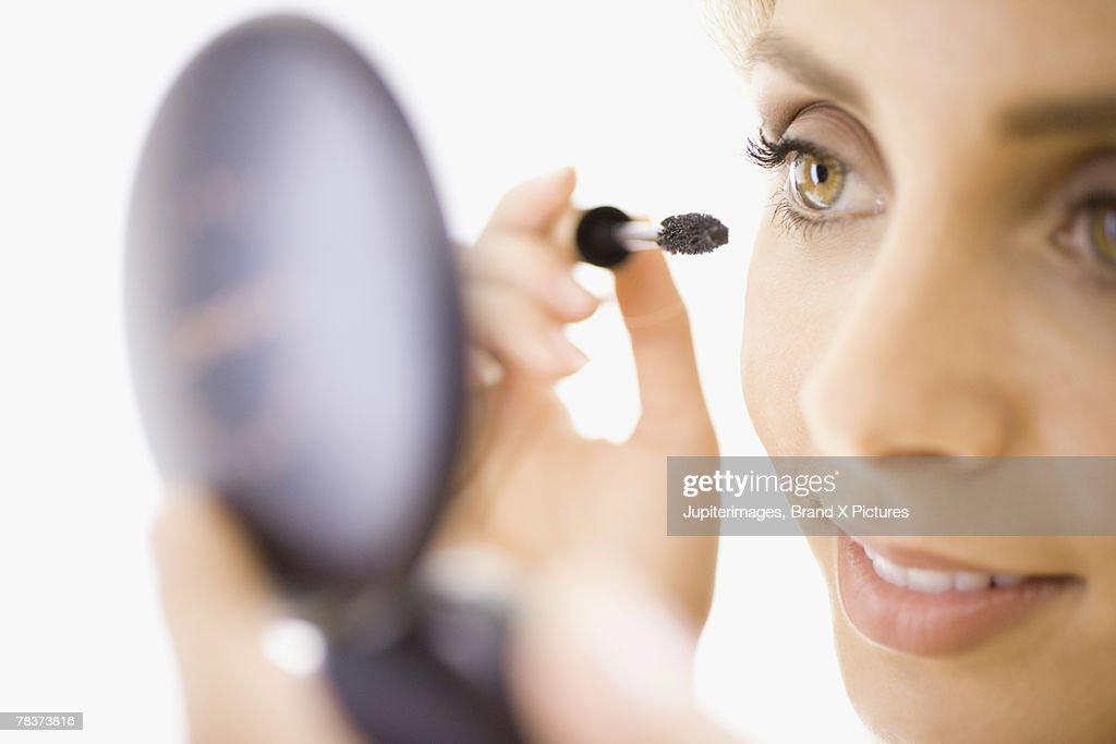 Close-up of woman applying makeup : Photo