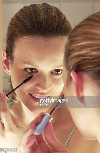 close-up of woman applying mascara and smiling - 20 24 jahre stock pictures, royalty-free photos & images